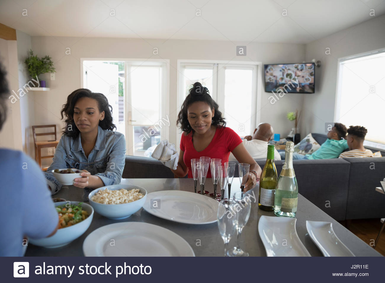 African American teenage sisters eating in kitchen - Stock Image