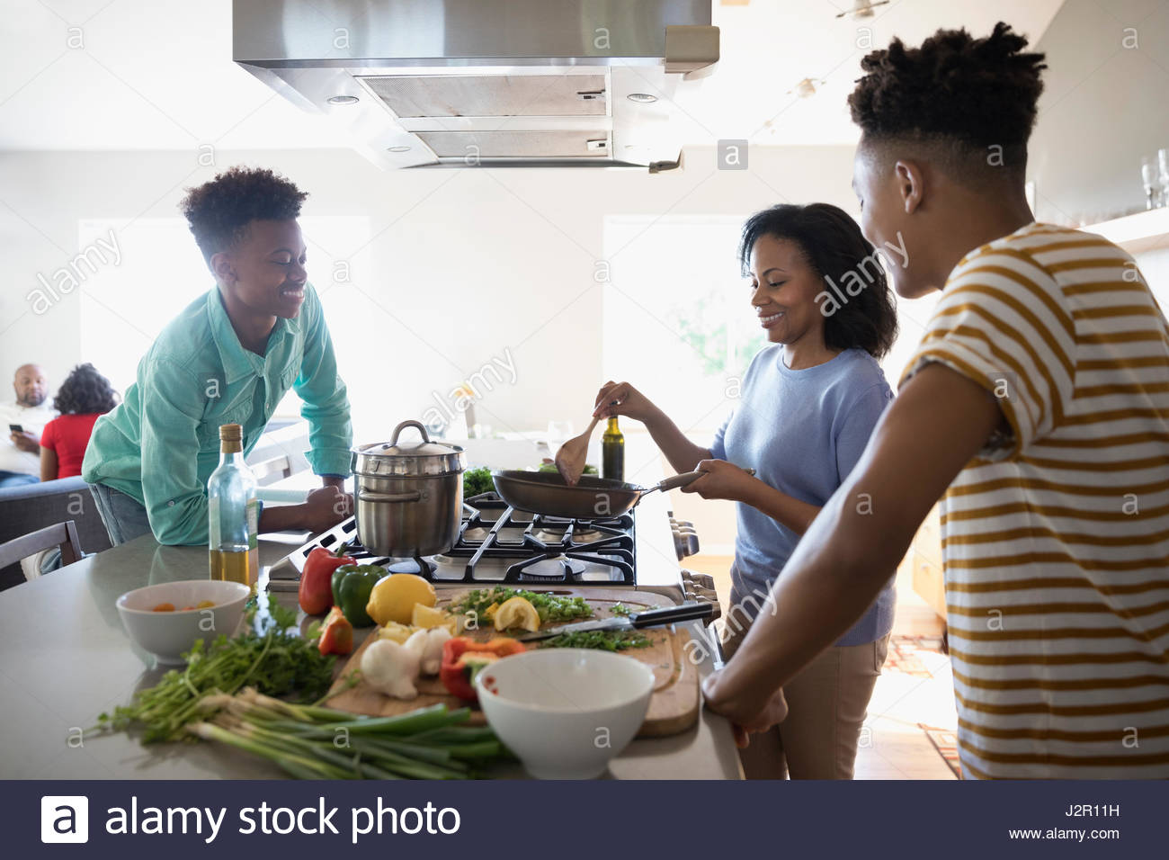 African American mother and teenage sons cooking at stove in kitchen - Stock Image
