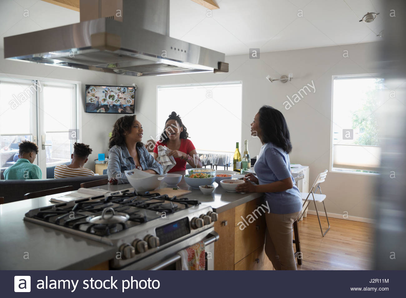 African American mother and teenage daughters cooking and eating in kitchen - Stock Image