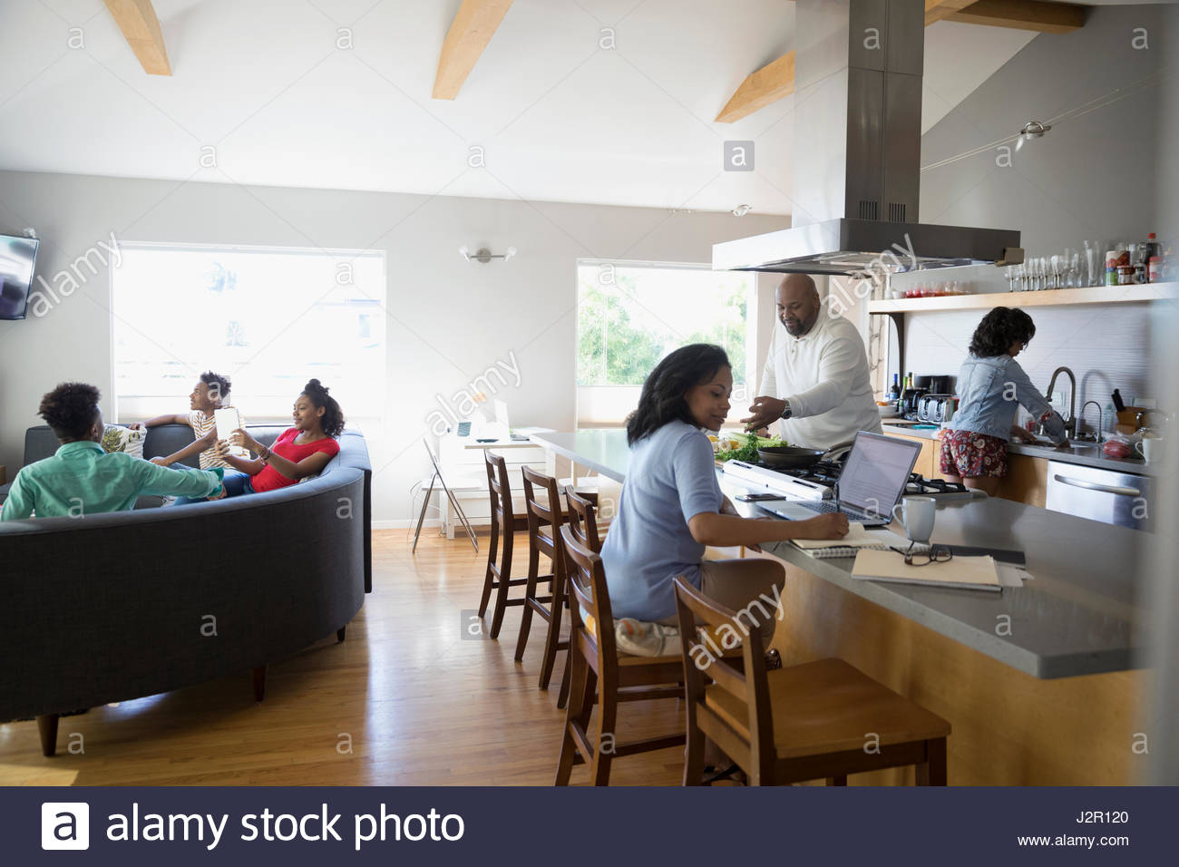 African American family cooking, working and watching TV in kitchen and living room - Stock Image