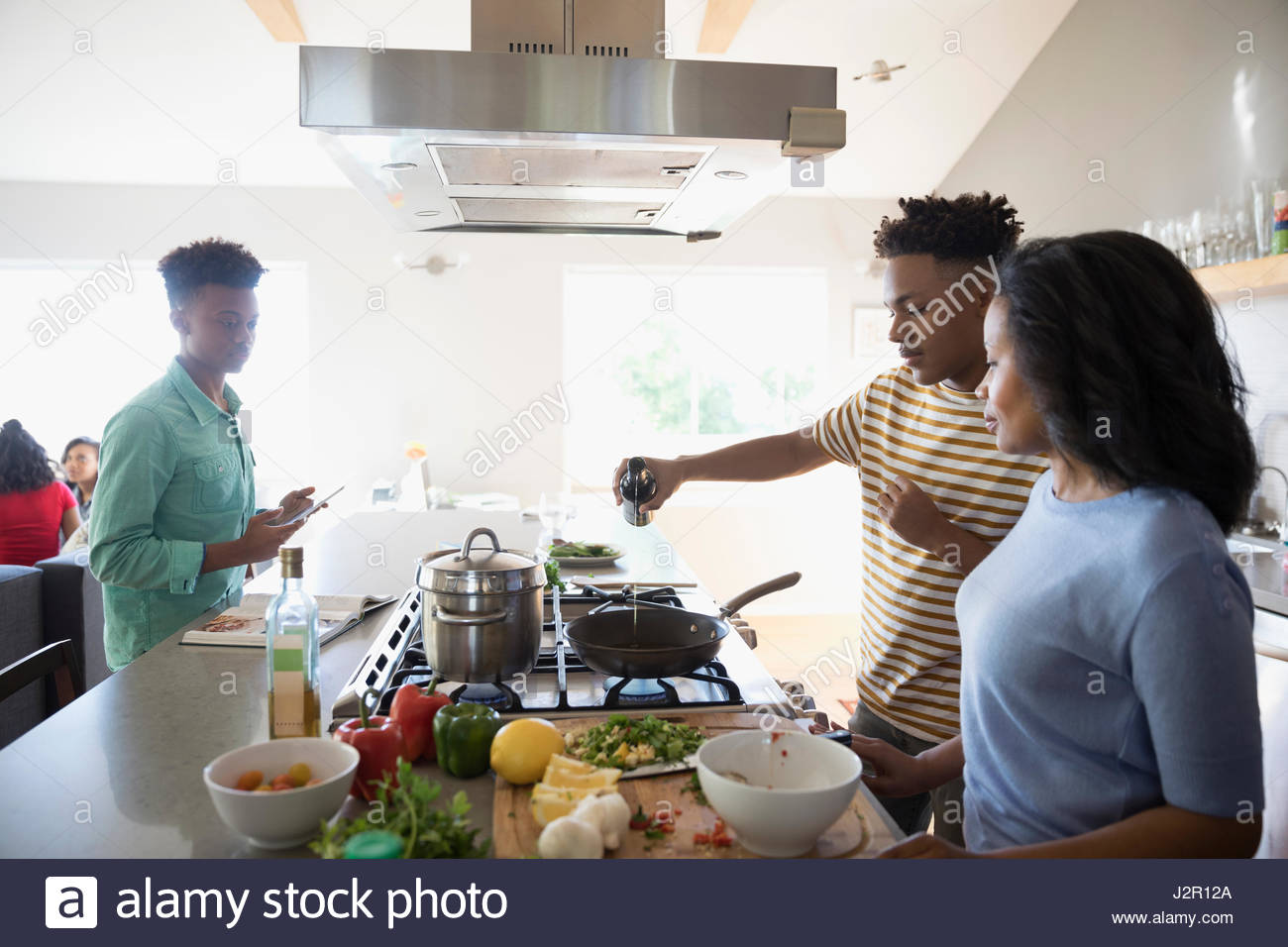 African American mother and teenage sons cooking in kitchen - Stock Image