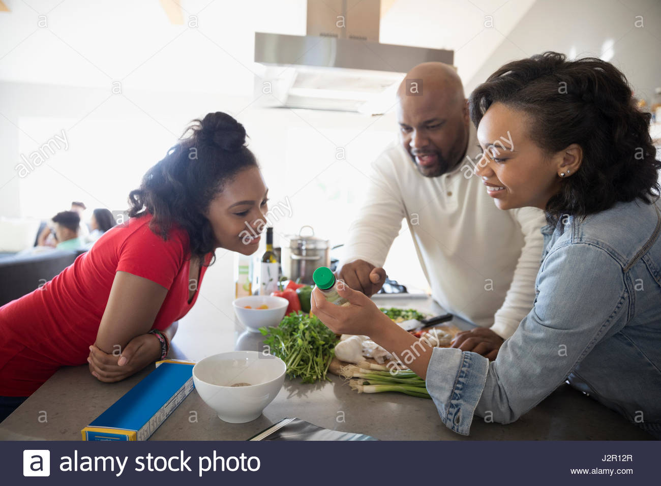 African American family cooking, looking at bottle in kitchen - Stock Image