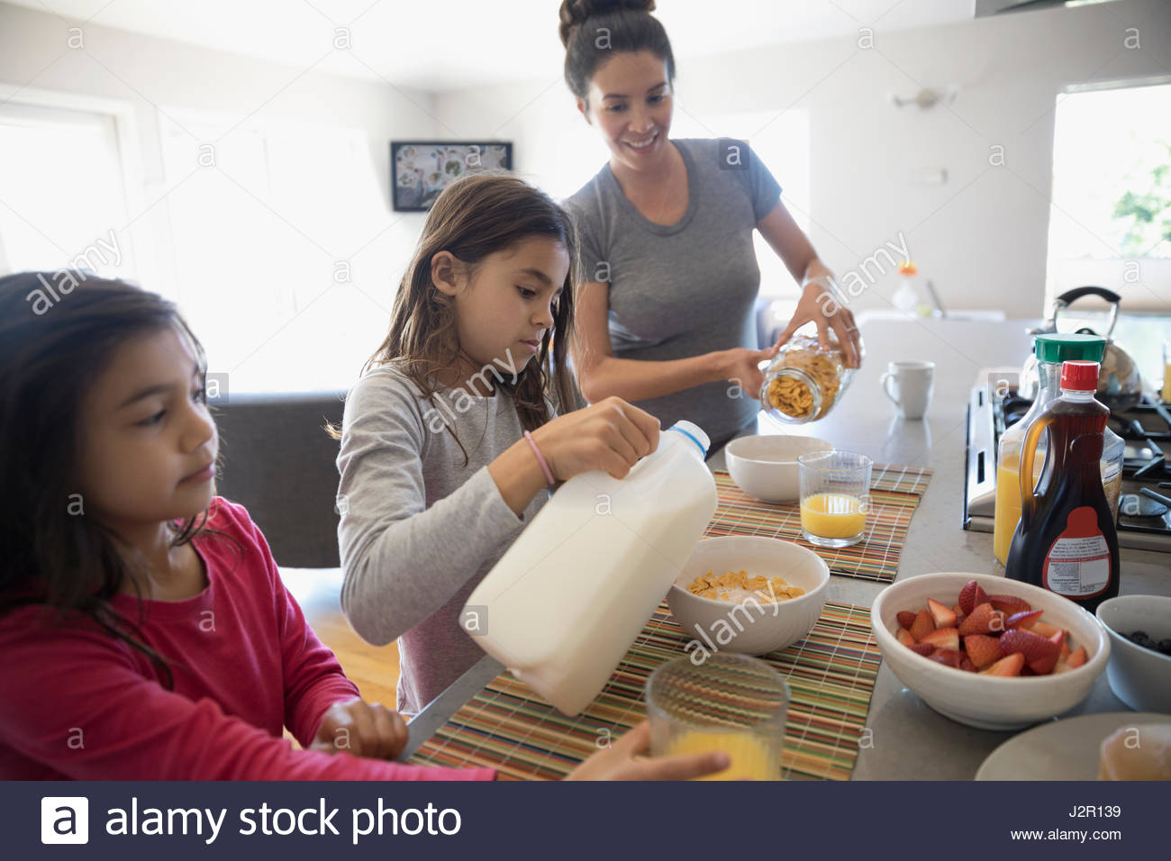 Mother and daughters eating breakfast in kitchen - Stock Image