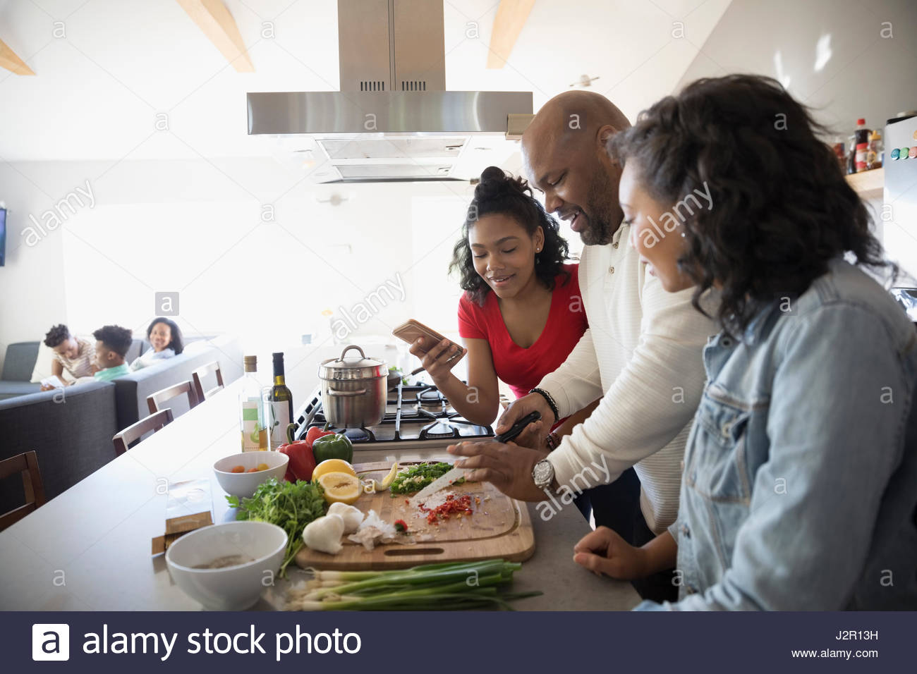 African American father and daughters cooking in kitchen - Stock Image