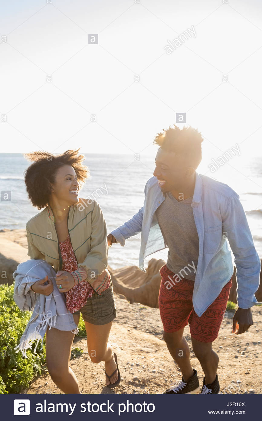 Playful young couple walking on sunny beach - Stock Image