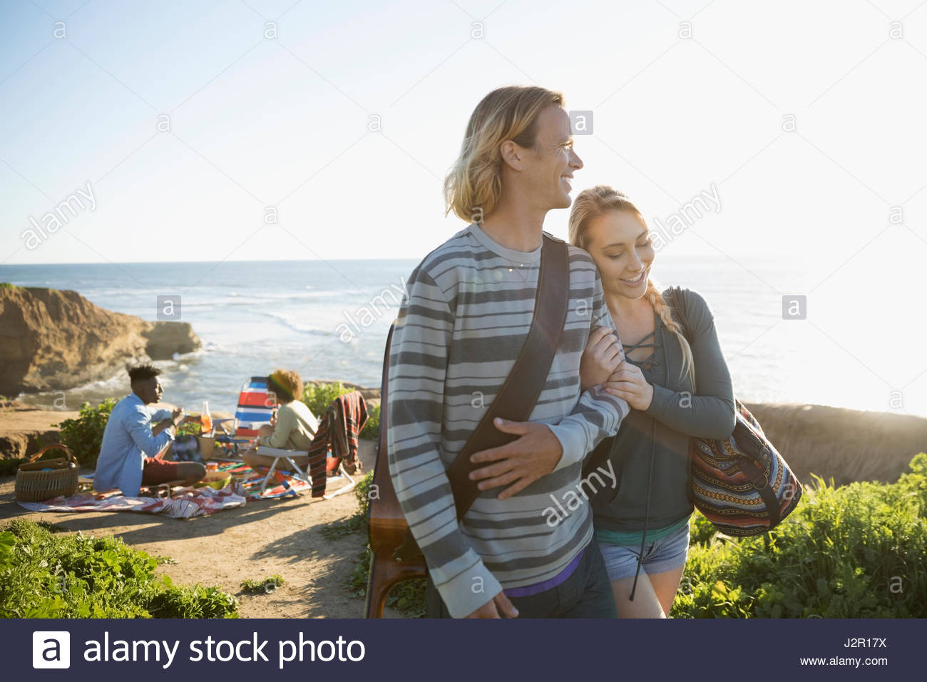 Affectionate young couple walking arm in arm with guitar on sunny beach Stock Photo