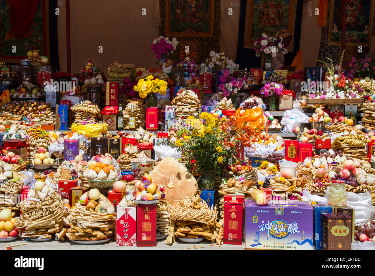 A large quantity of food offered at a Buddhist Ritual Ceremony in a Buddhist region of Qinghai Province in China - Stock Image