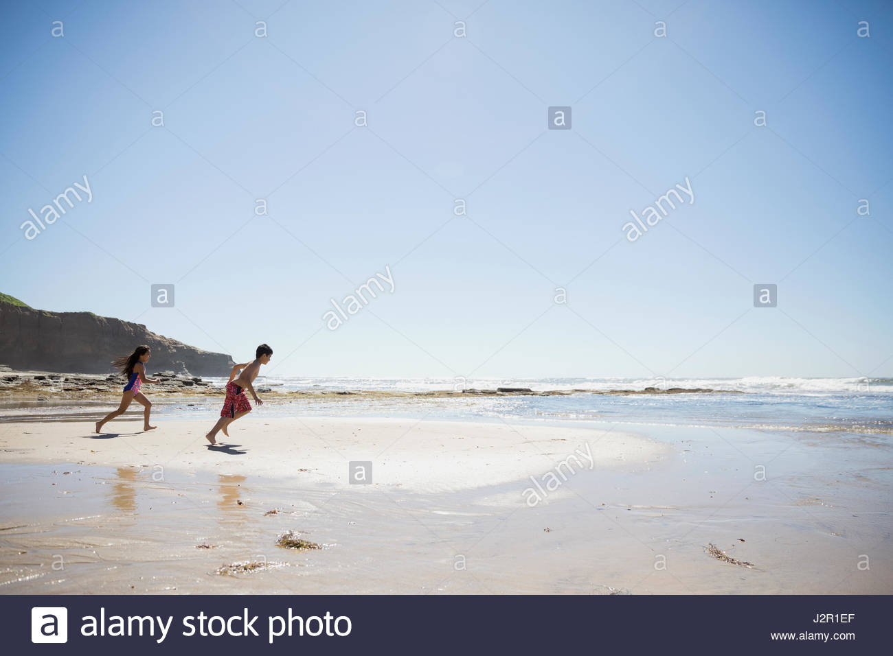 Latino brother and sister running on sunny beach - Stock Image