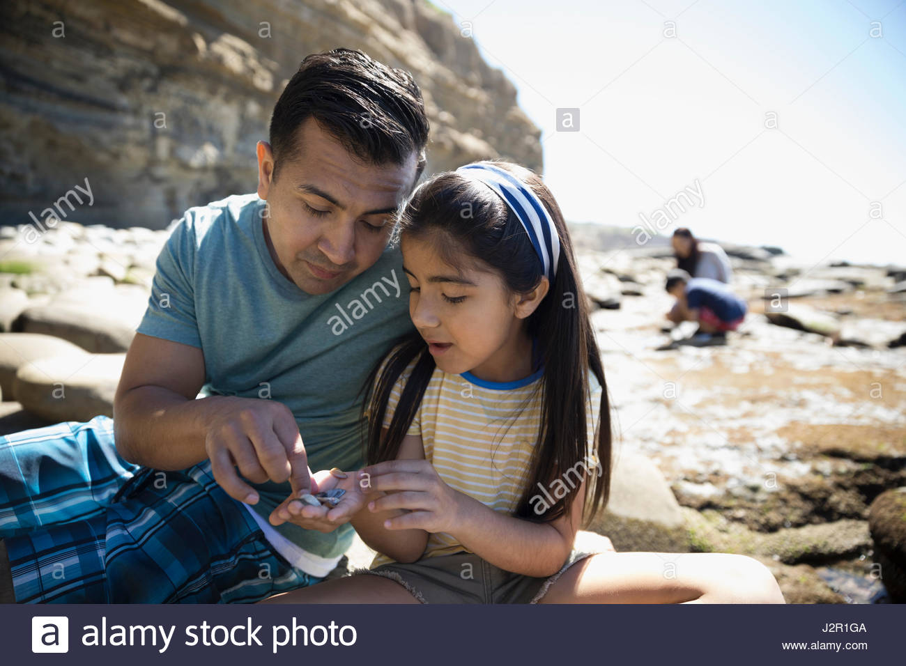 Latino father and daughter looking at rocks on sunny beach - Stock Image