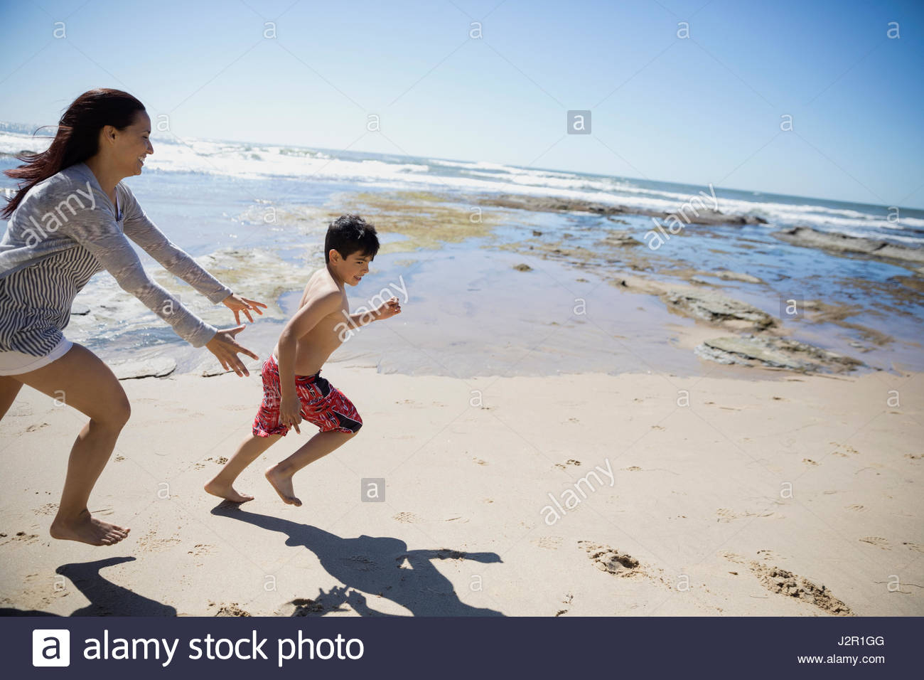 Latino mother chasing son on sunny beach - Stock Image