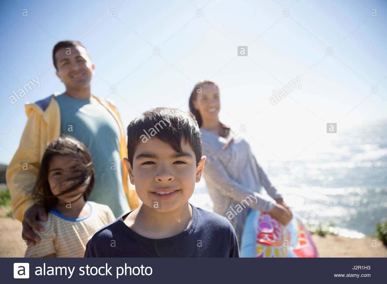 Portrait smiling Latino boy with family on sunny beach - Stock Image