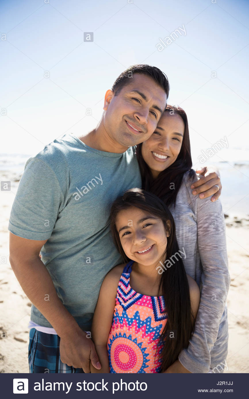 Portrait smiling Latino family hugging on sunny beach Stock Photo