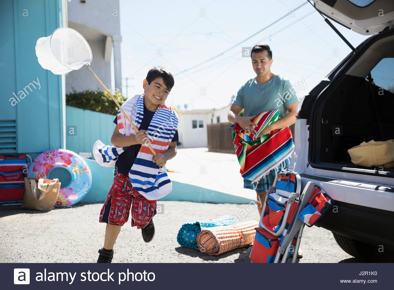 Father and son loading car for beach trip in sunny driveway Stock Photo