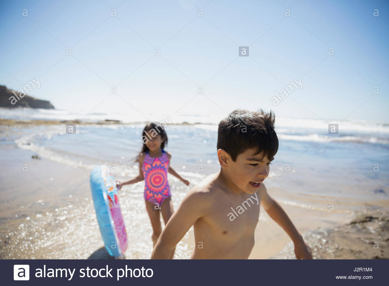 Latino brother and sister with inflatable ring on sunny beach - Stock Image