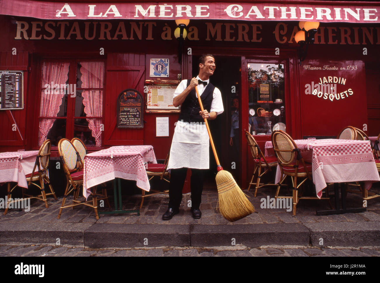 PARIS WAITER MONTMARTRE Typical French waiter, sweeping  preparations at renowned Parisian restaurant 'A La - Stock Image