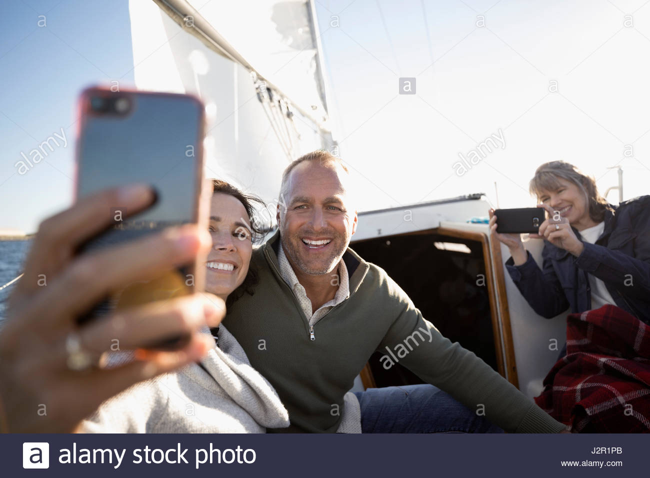 Senior couple with camera phone taking selfie on sailboat - Stock Image