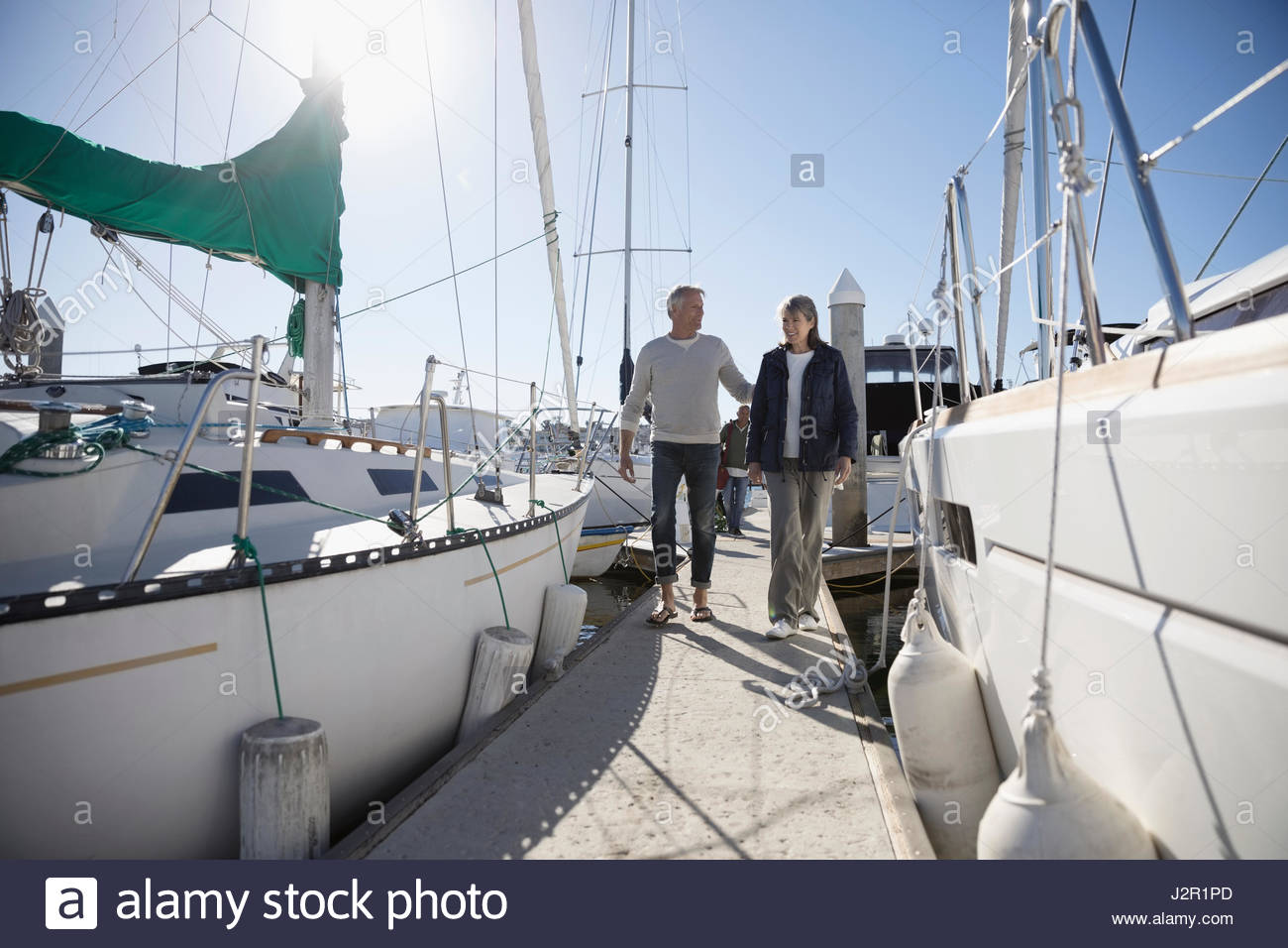 Senior couple walking among sailboats in sunny harbor - Stock Image