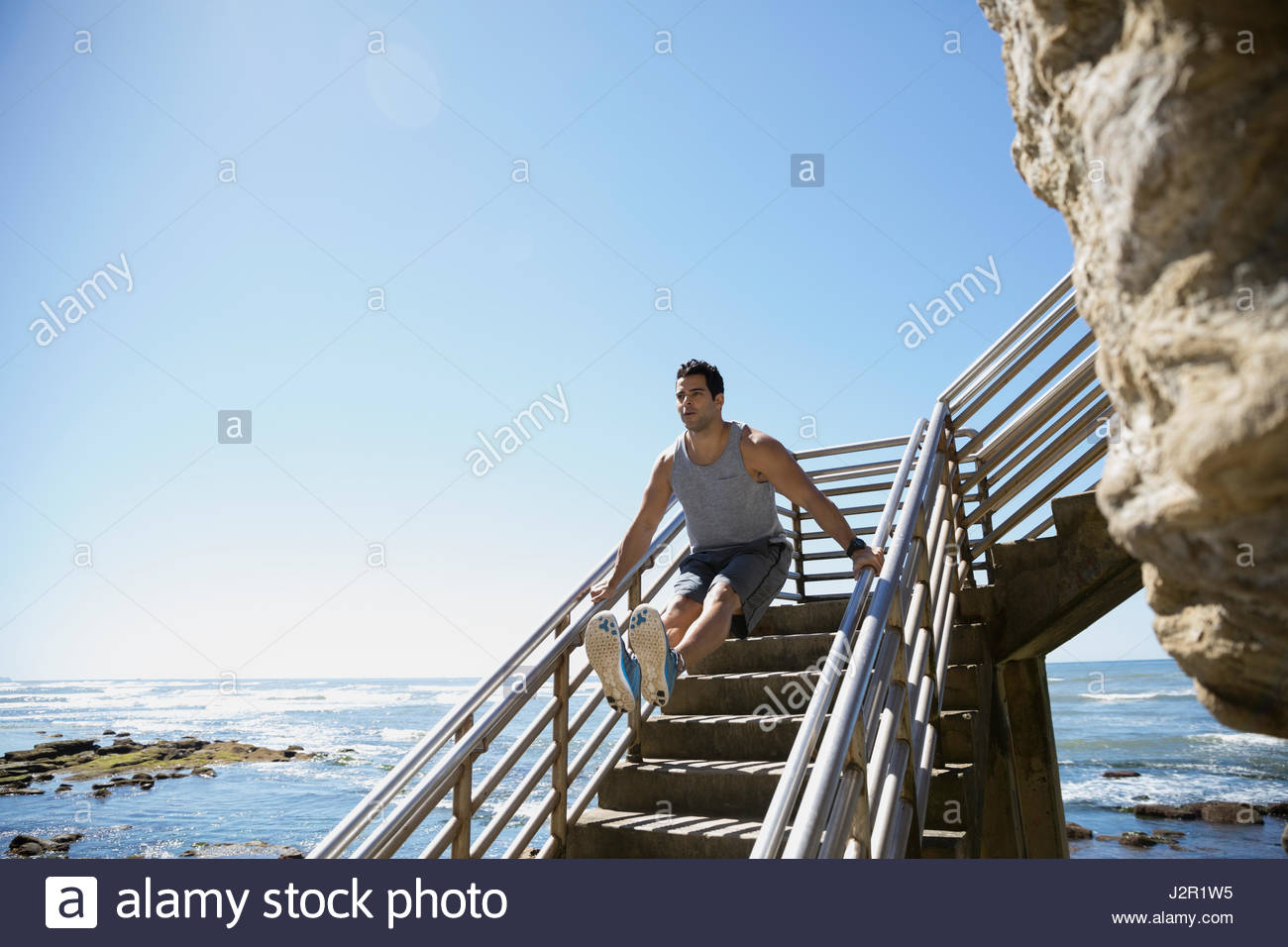 Young Middle Eastern man exercising, doing leg lift on stairs above sunny ocean - Stock Image