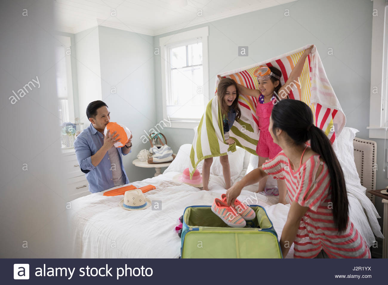 Family packing for vacation, playing on bed - Stock Image