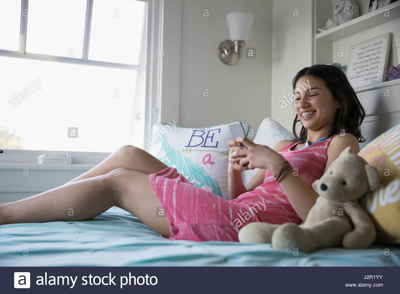 Smiling teenage girl with braces texting with smart phone on bed - Stock Image
