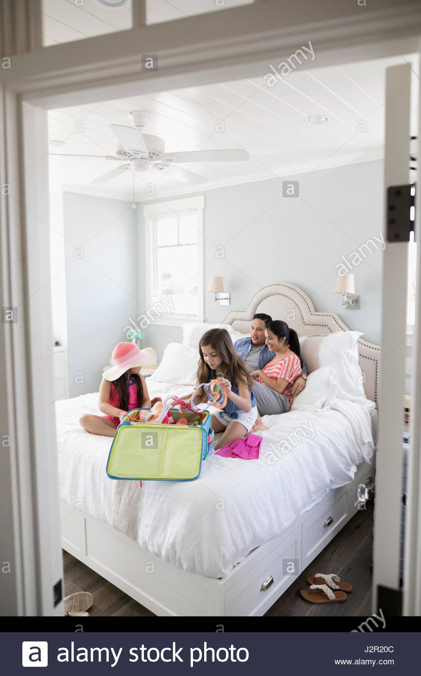 Family packing for vacation on bed - Stock Image