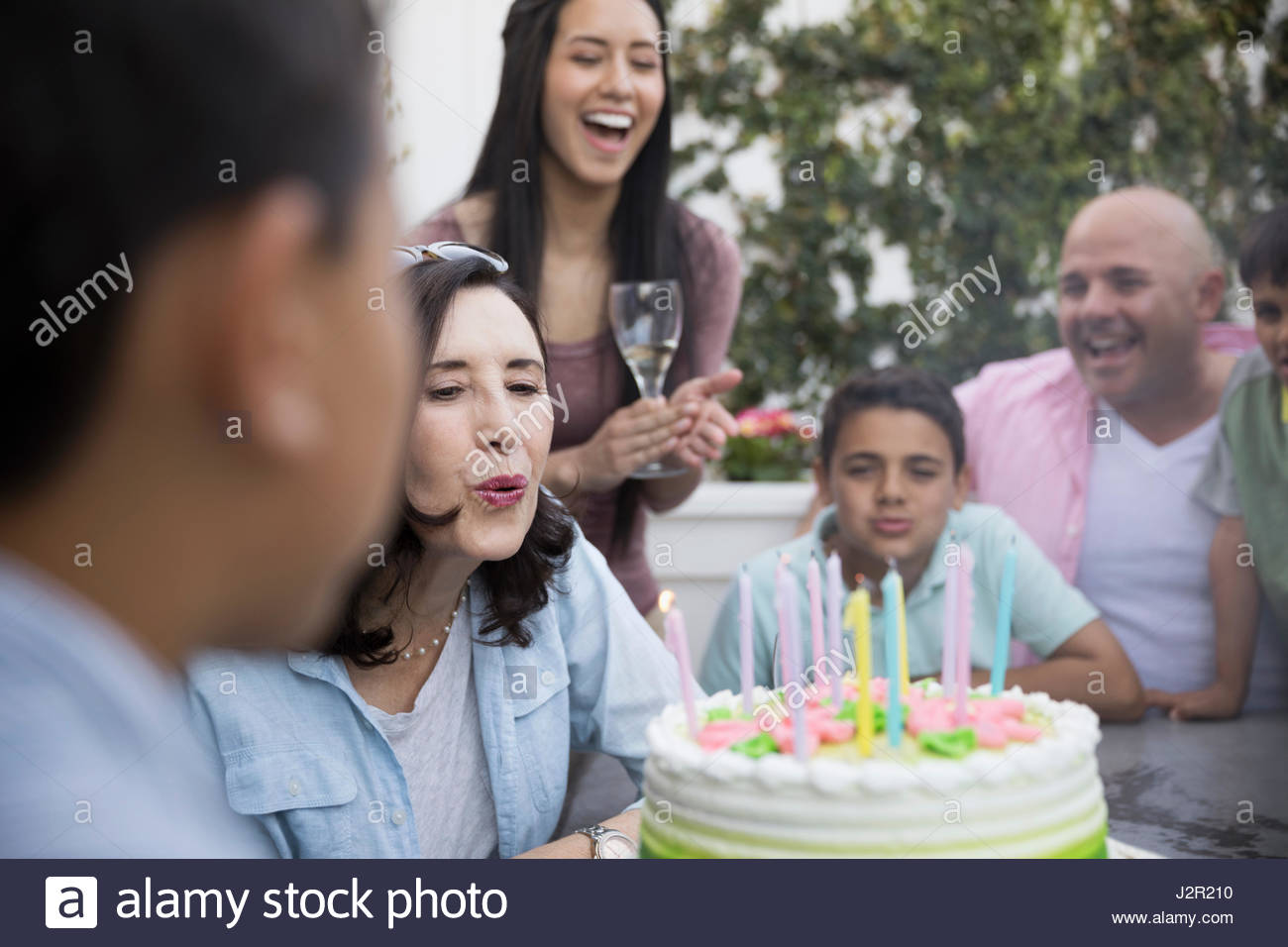 Multi-generation family celebrating birthday, blowing out candles on cake - Stock Image