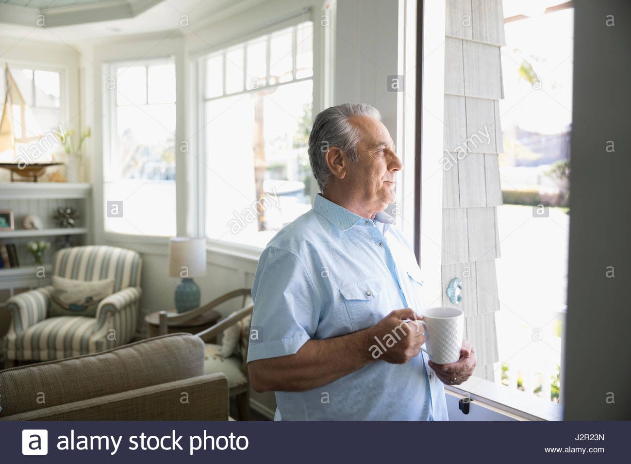 Senior man drinking coffee and looking out window in beach house - Stock Image