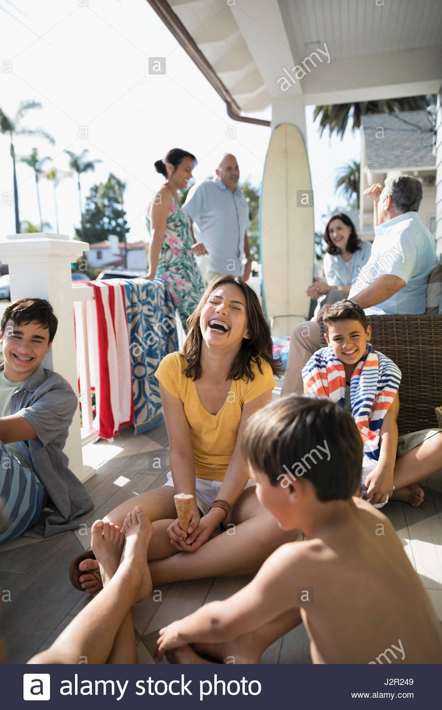 Laughing brothers and sister eating ice cream cone on summer beach house porch - Stock Image