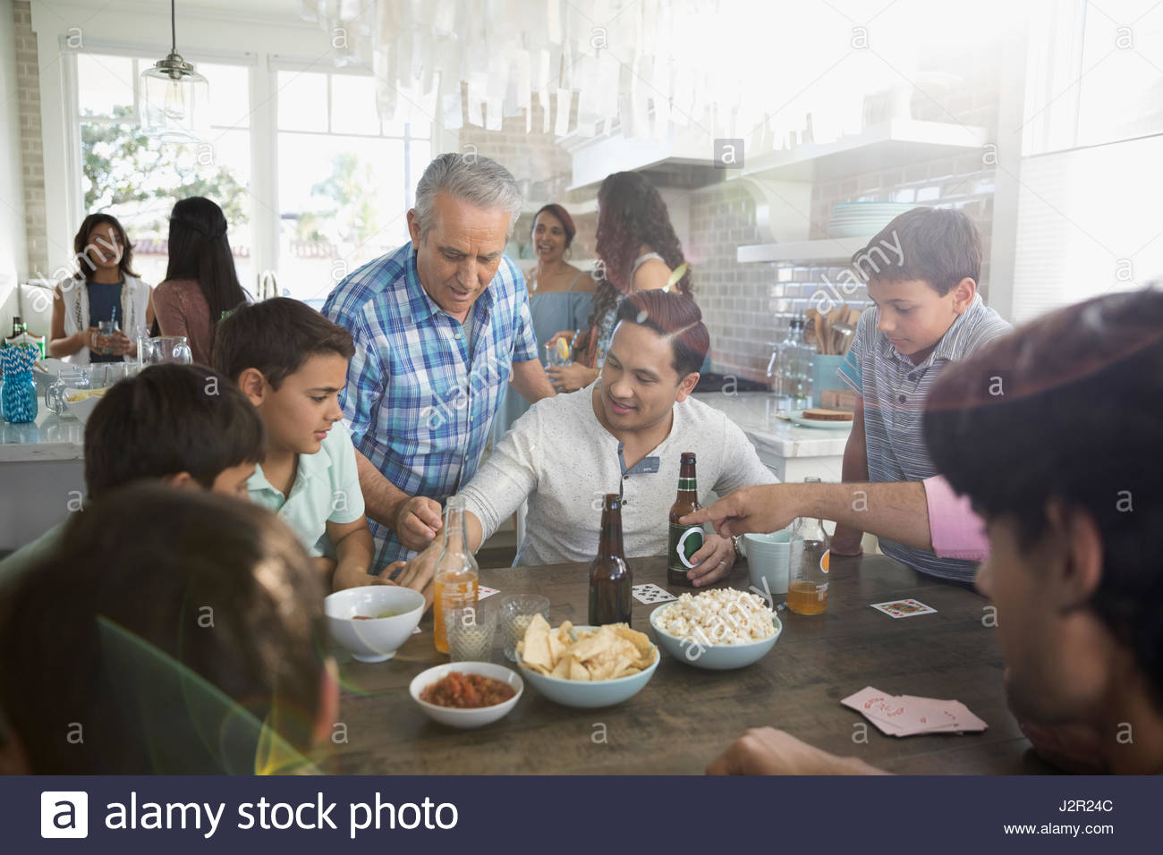 Multi-generation family playing cards, eating and drinking at beach house kitchen table - Stock Image
