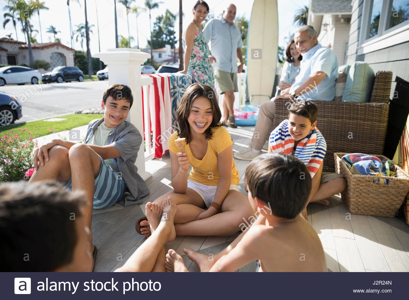 Brothers and sister eating ice cream cone on summer beach house porch - Stock Image