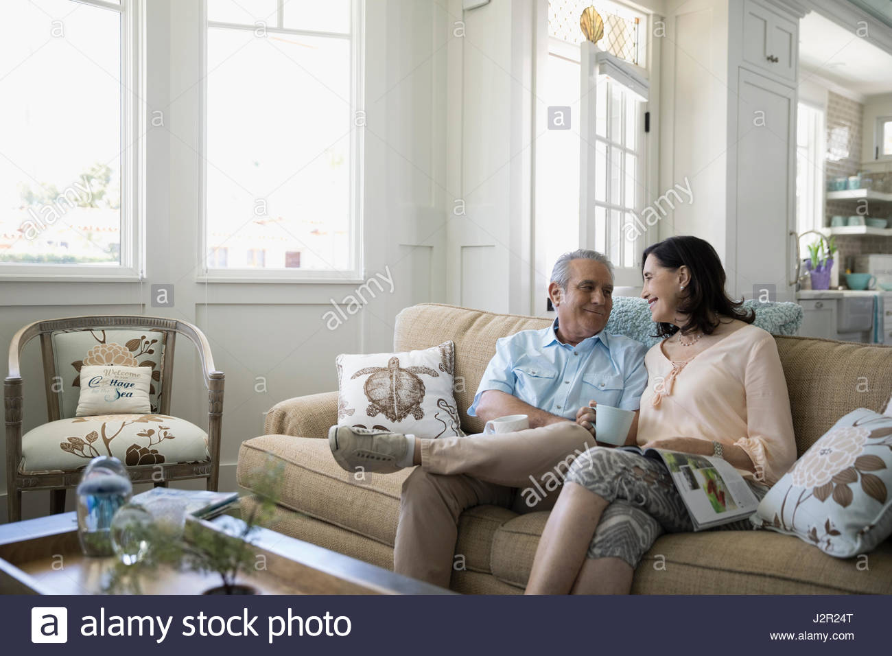 Senior couple drinking coffee and talking in beach house living room ...