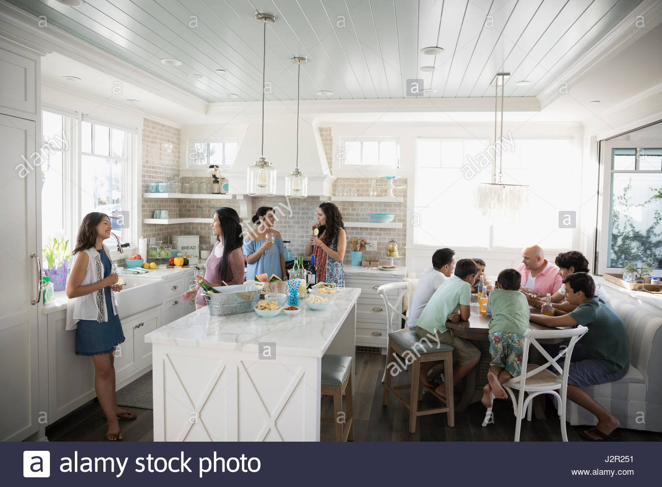 Family and friends eating and drinking in beach house kitchen - Stock Image