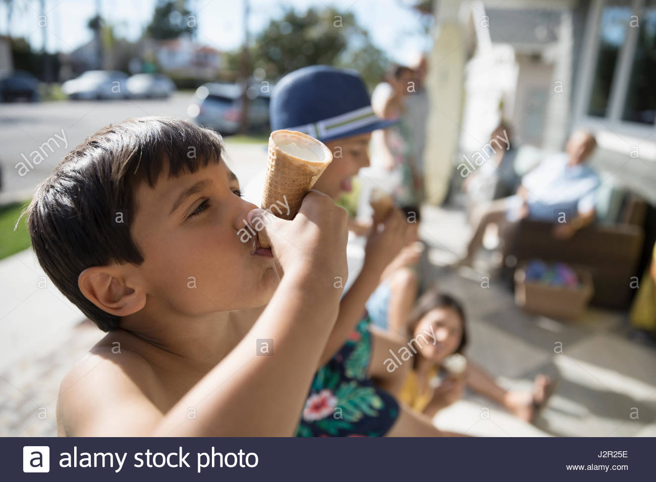 Boy eating melting ice cream cone on summer beach house porch - Stock Image