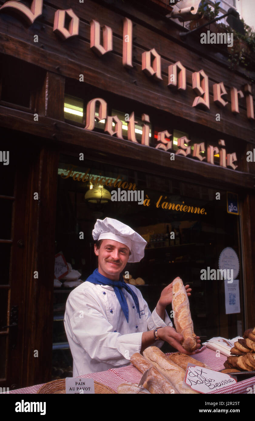 HONFLEUR FRANCE Traditional Boulangerie Baker posing with freshly baked French Baguette, standing outside with his - Stock Image
