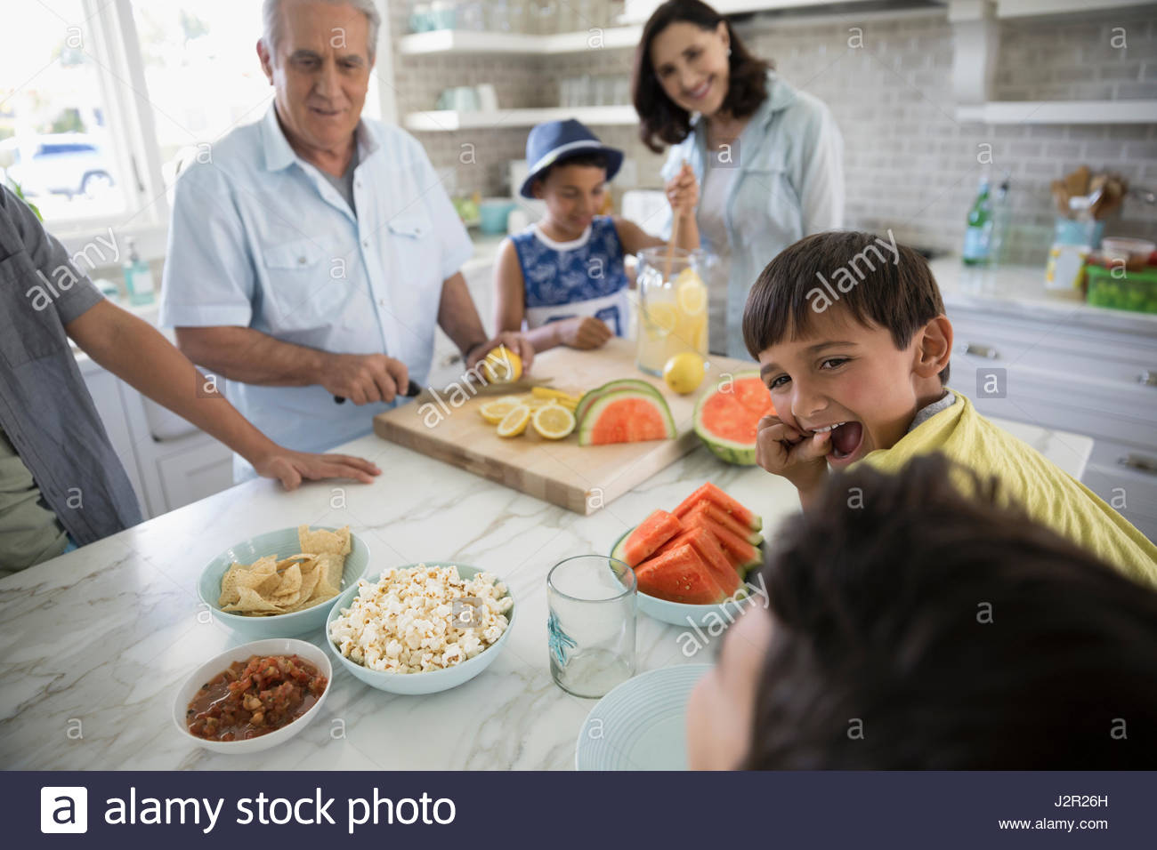 Multi-generation family making lemonade and snacking in kitchen - Stock Image
