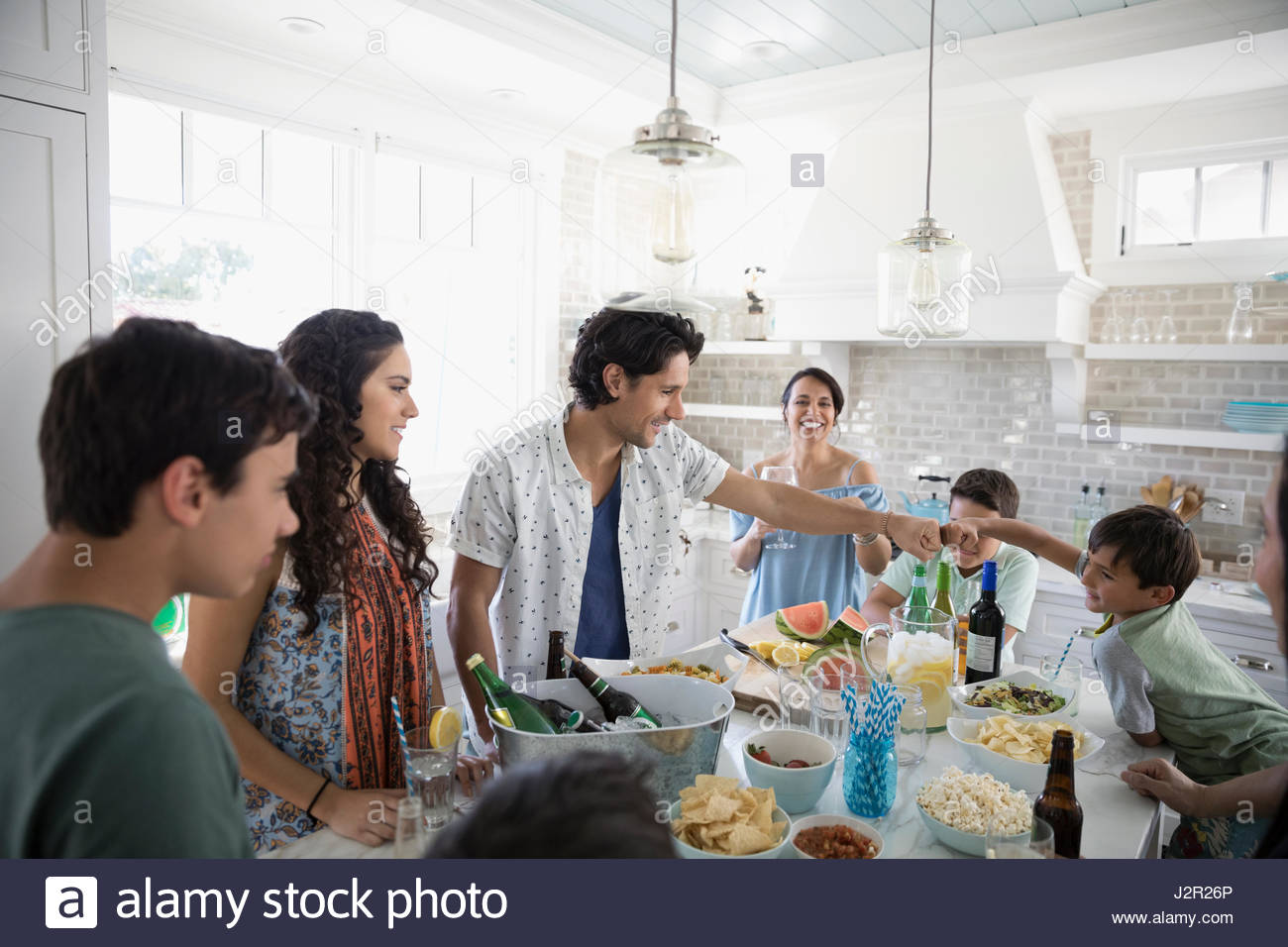Family and friends drinking and eating in beach house kitchen, father and son fist bump - Stock Image