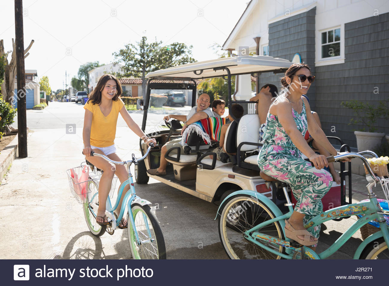 Family with beach cruiser bicycles and golf cart in summer beach house driveway - Stock Image