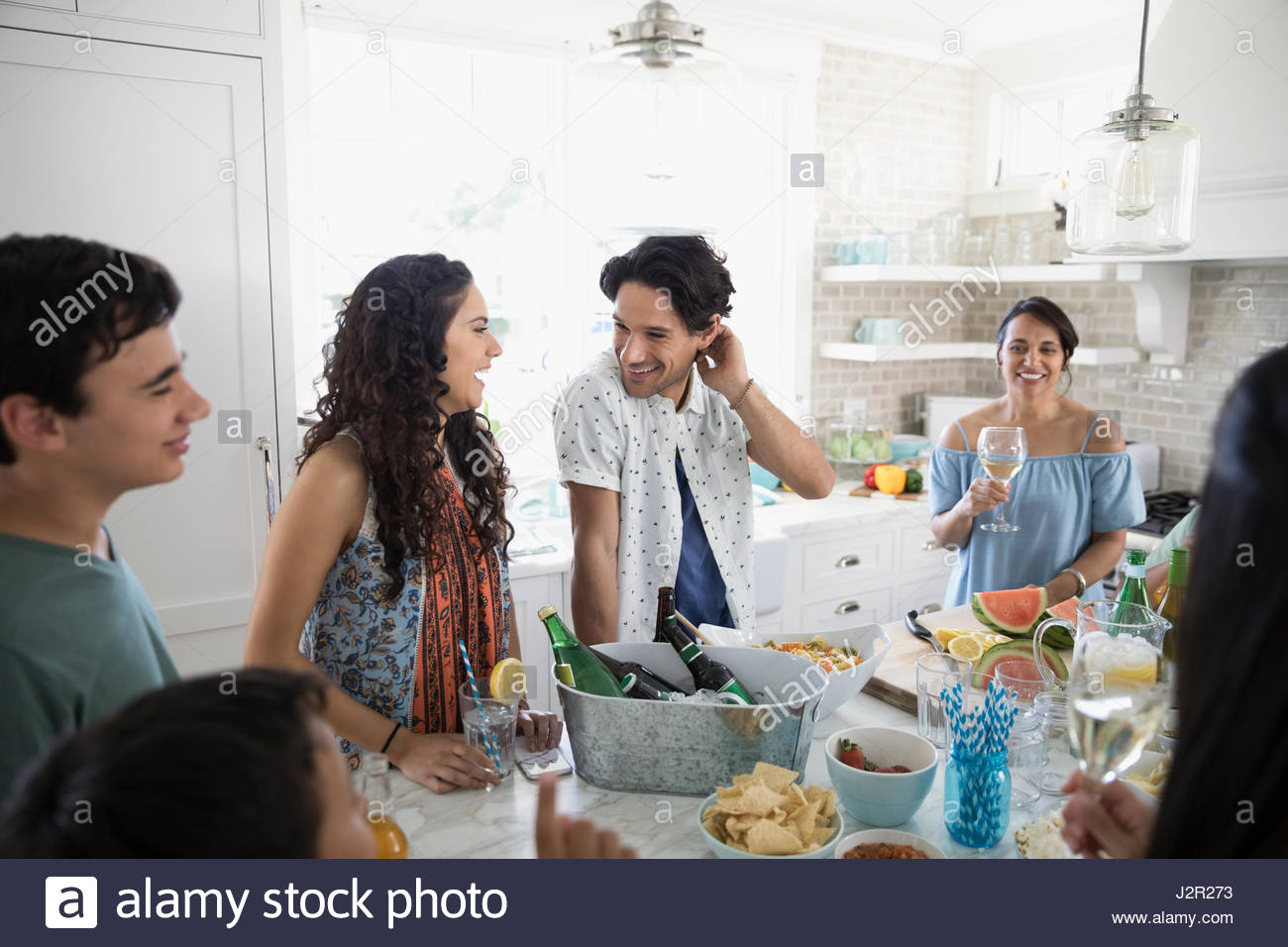 Family and friends drinking and eating in beach house kitchen - Stock Image