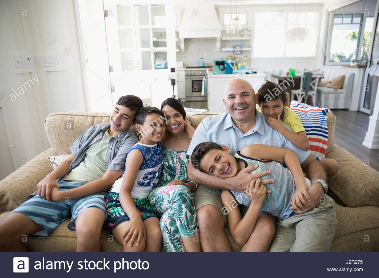 Portrait smiling family in beach house living room - Stock Image