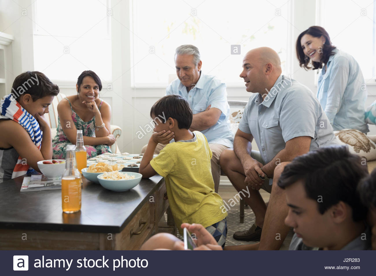 Multi-generation family playing checkers and using digital tablet in beach house living room Stock Photo