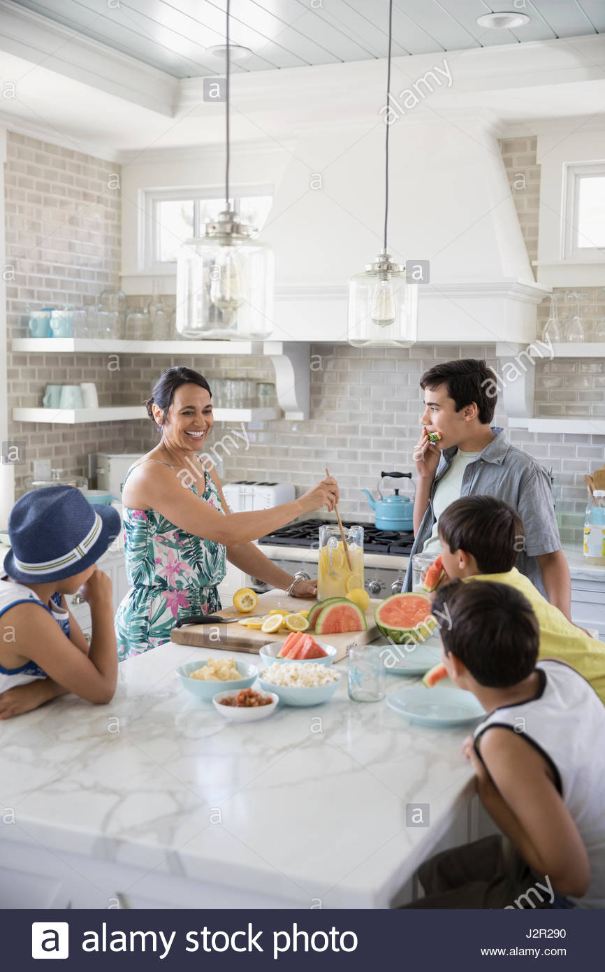 Mother and sons making lemonade and snacking in kitchen - Stock Image