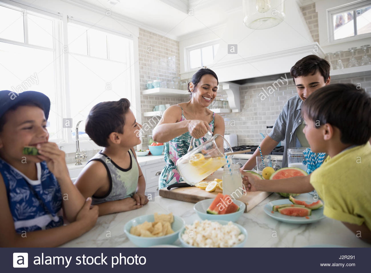 Mother pouring lemonade for sons in kitchen - Stock Image