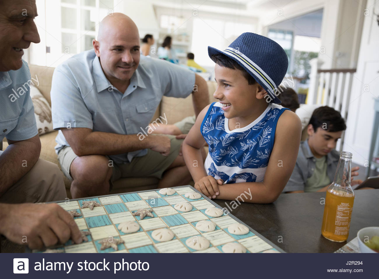 Multi-generation family playing checkers in beach house Stock Photo