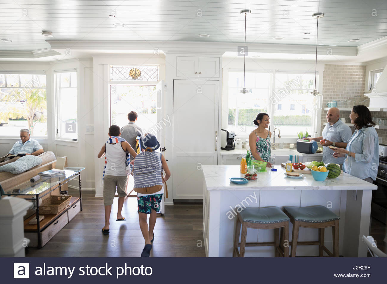 Brothers in swim trunks leaving beach house - Stock Image