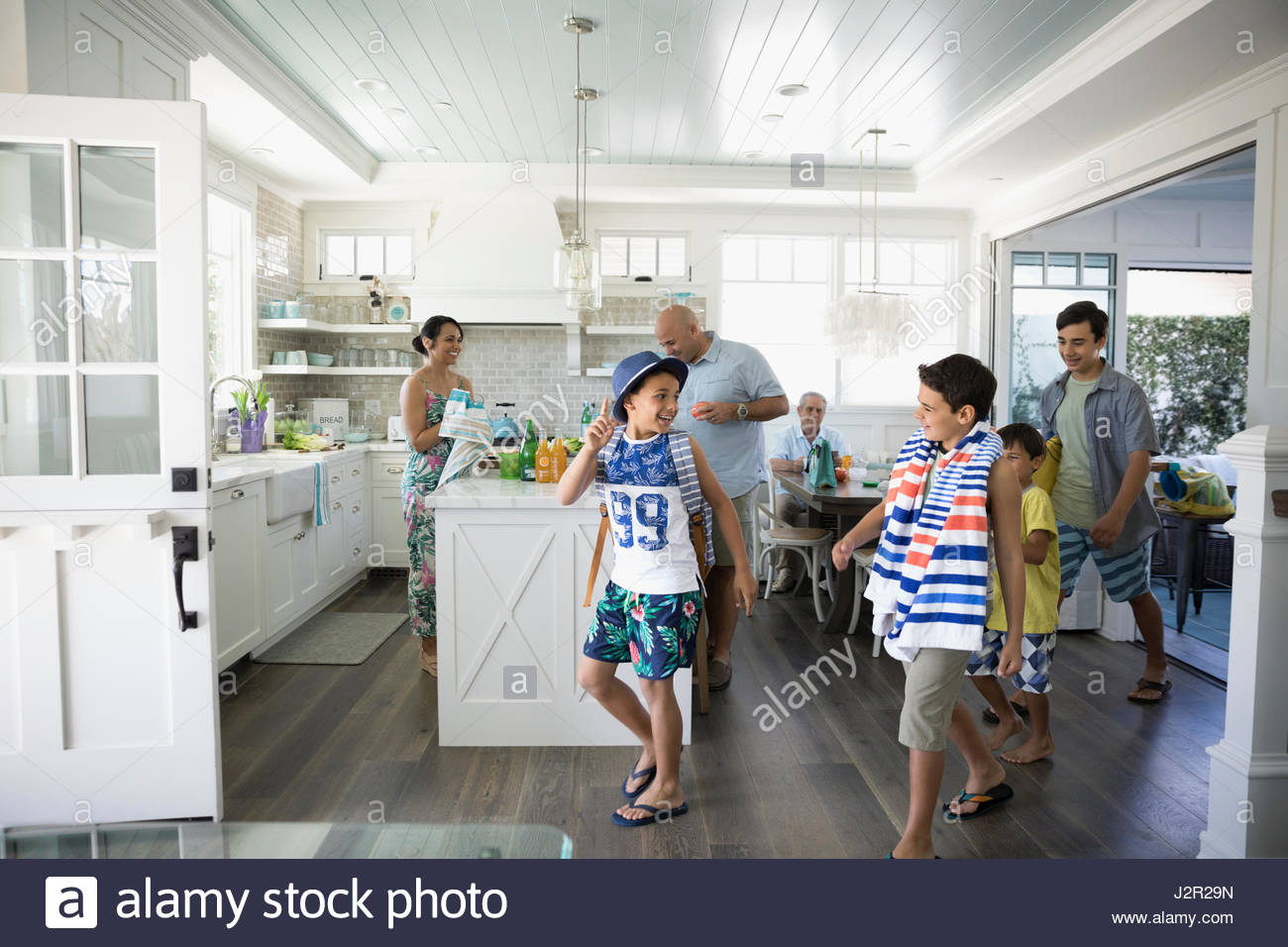 Brothers in swim trunks with beach towel leaving beach house - Stock Image