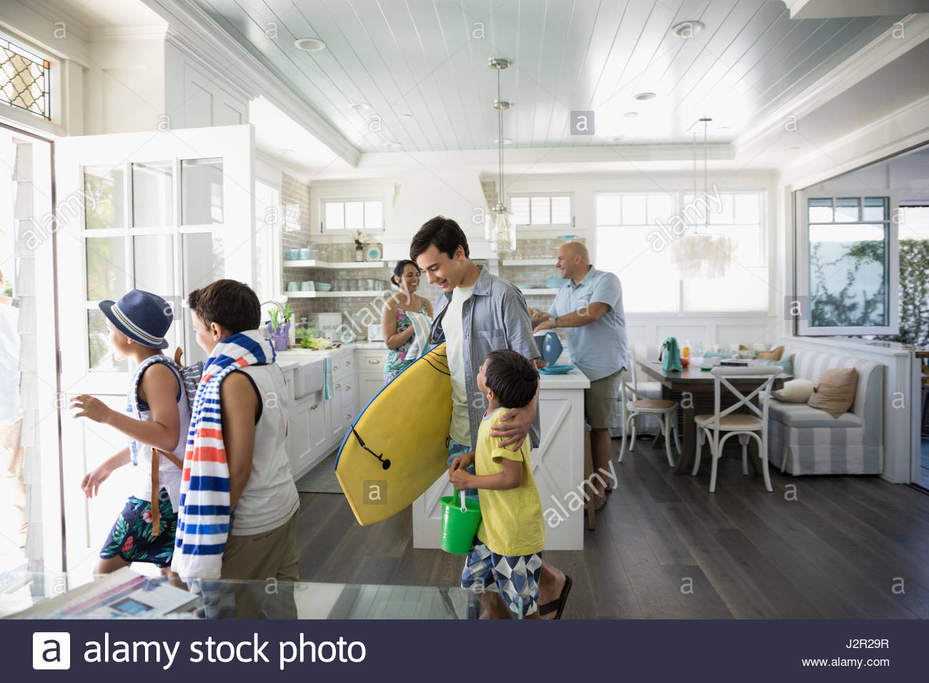 Family with body board and beach towel leaving beach house - Stock Image
