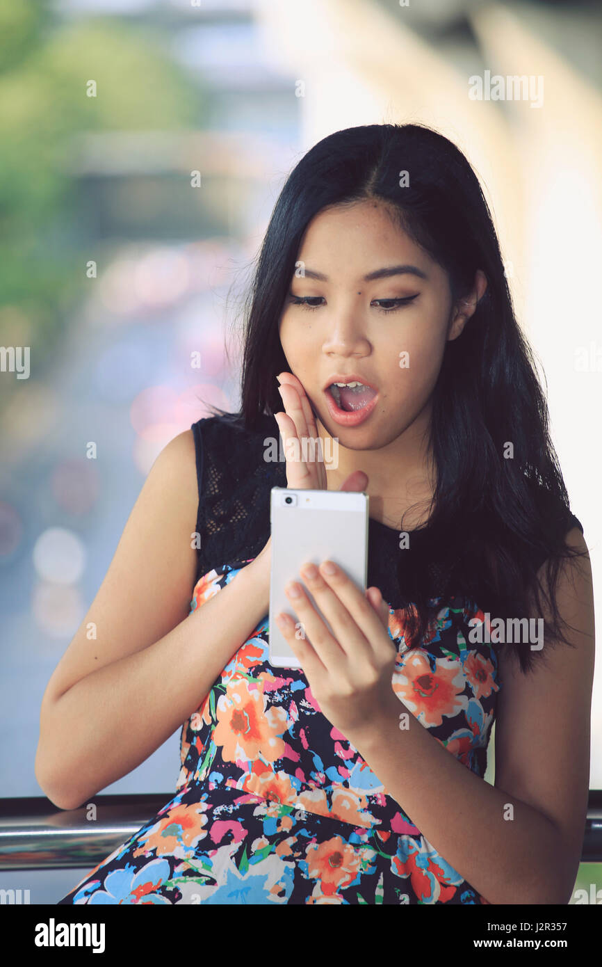 Asian woman looking surprised at her mobile phone - Stock Image