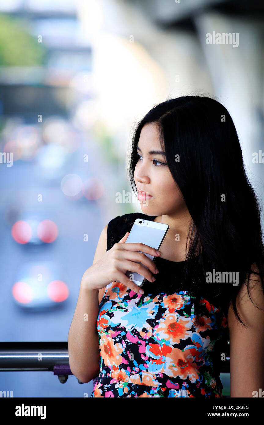 Thoughtful Asian woman reflects - Stock Image