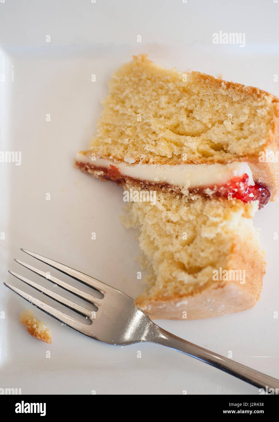 Food; Coffee and Cake; Victoria Sponge Cake; Dessert; Pudding; Sweet; Treat; Baked; Baking; Fork; Plate; Partially - Stock Image