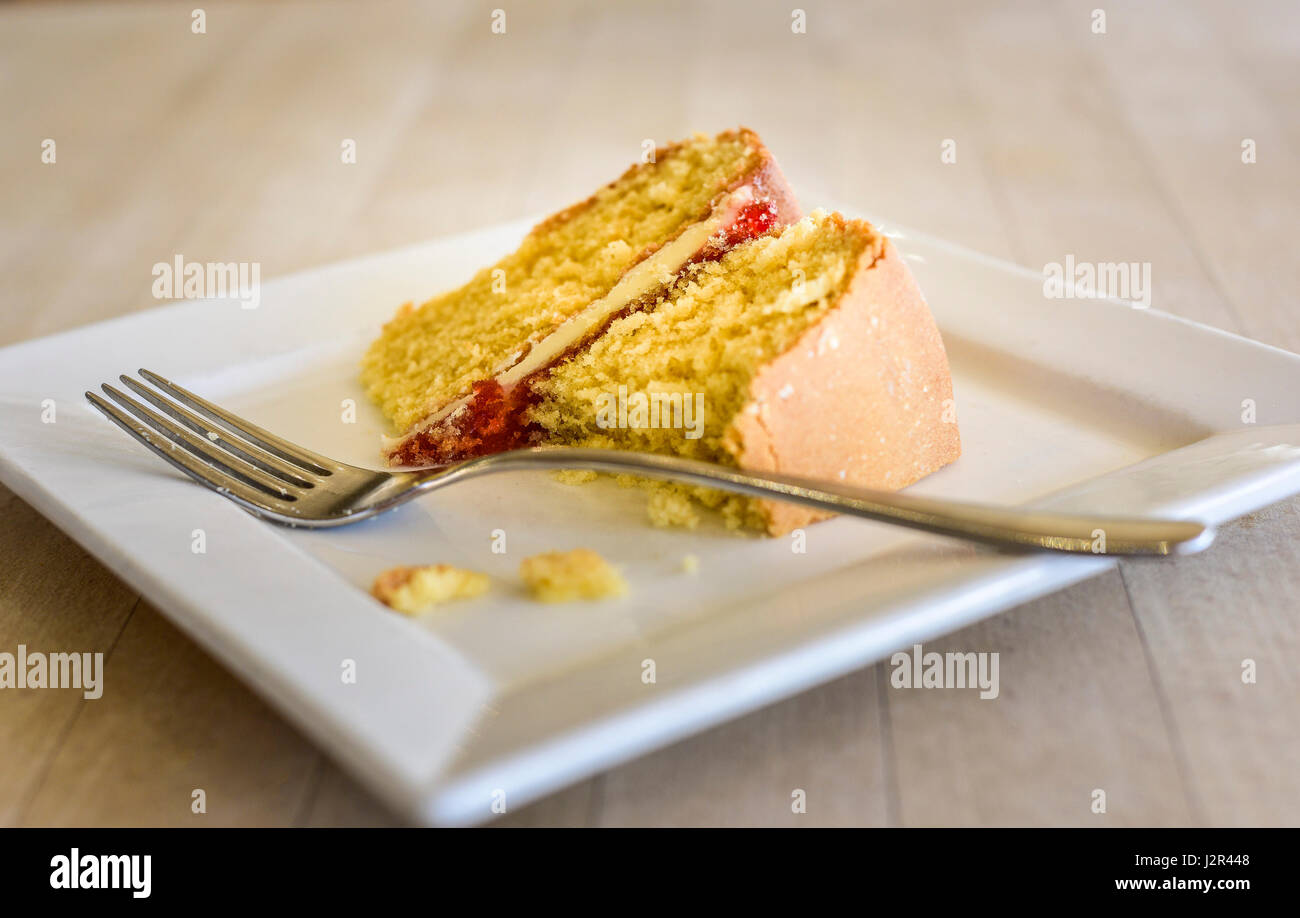 Food Victoria Sponge Cake partially eaten Dessert Pudding Sweet Treat Baked Baking Fork Plate Relaxation Afternoon - Stock Image
